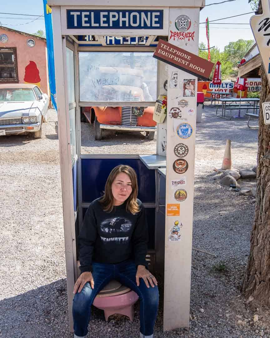 Lindsay sitting on a toilet in a phone booth