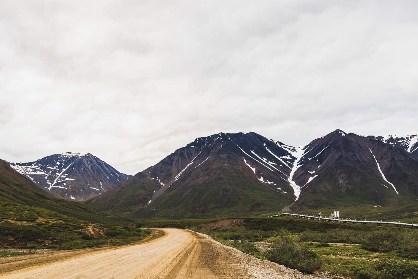 Dirt road going into snow covered mountains
