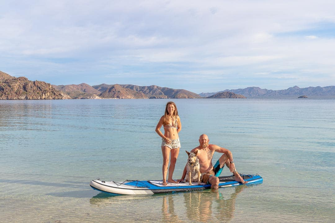 Couple with dog on a paddleboard in the ocean