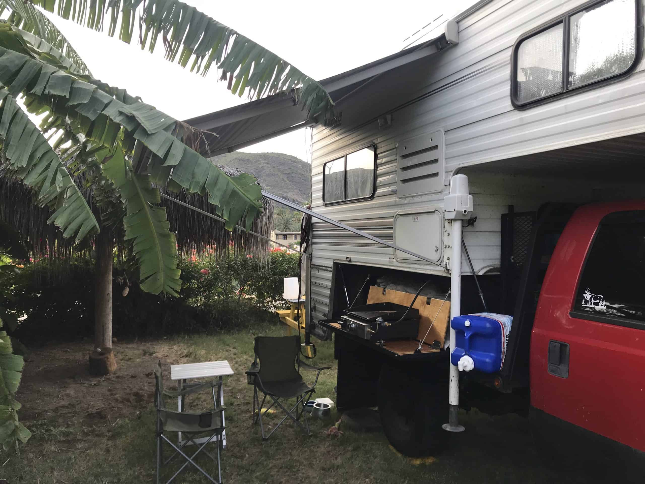 truck camper with chairs, table and grill set up outside
