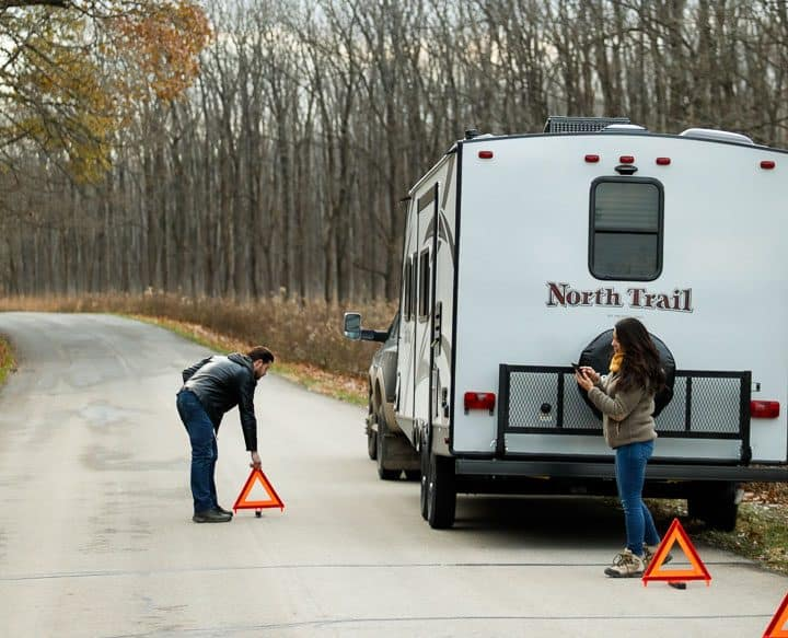 Person putting out emergency triangles around broken down RV